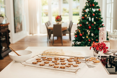 Foto de Tray of baked star cookies and dough placed on kitchen table. Decorated Christmas tree in the background. - Imagen libre de derechos