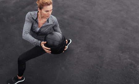 Photo for Fitness woman working out at outdoors gym using medicine ball. Sportswoman stretching outdoors with medicine ball. Copyspace for text. - Royalty Free Image