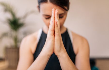 Photo pour Close up of woman hands joined. Female meditating with her hands joined indoors. Namaste yoga pose, meditating, breathing and relaxing. - image libre de droit