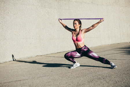 Photo pour Strong young woman stretching with resistance band. Fitness female athlete exercising outdoors. - image libre de droit