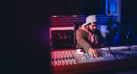 Photo for Sound recording studio mixing desk with engineer. Music producer working at audio control panel. Musician working and producing music in his modern recording studio. - Royalty Free Image