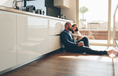 Photo for Young man and woman sitting on floor in kitchen and talking. Loving young couple spending time together at home. - Royalty Free Image