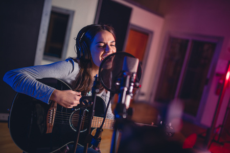Photo for Female vocal artist singing in a recording studio with guitar. Woman singer singing a song and playing guitar. - Royalty Free Image