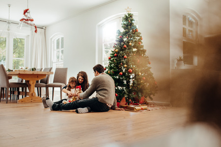 Foto de Family sitting near Christmas tree opening gift boxes. Young couple helping their daughter open Christmas gifts. - Imagen libre de derechos