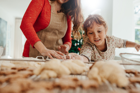 Photo for Mother and child making Christmas cookies. Daughter placing cookie dough on baking tray while mother cutting cookies with cutter. - Royalty Free Image