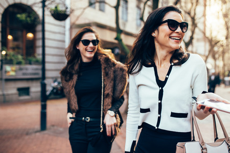 Foto de Two women on city street having fun. Female friends on walking down the road and smiling outdoors. - Imagen libre de derechos