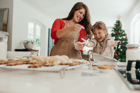 Foto de Happy mother and daughter playing with cookie flour at kitchen table while making Christmas cookies. Baked cookies and muffins on the kitchen table for Christmas. - Imagen libre de derechos