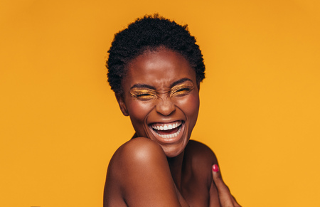 Foto de Cheerful young african woman with vivid makeup on her eyes. Female model laughing against yellow background. - Imagen libre de derechos