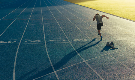 Photo pour Athlete running on an all-weather running track alone. Runner sprinting on a blue rubberized running track starting off using a starting block. - image libre de droit