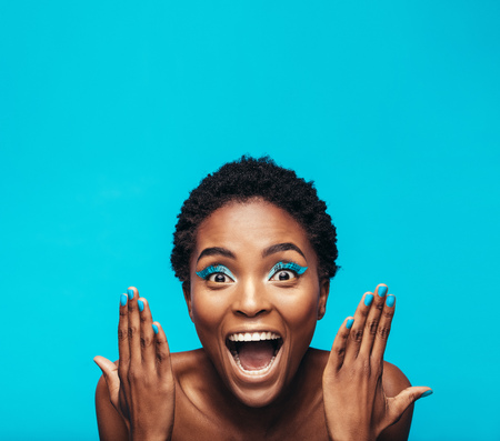 Photo pour Excited young woman with vibrant eye shadow and nail paint. Female model showing her vivid makeup against blue background. - image libre de droit