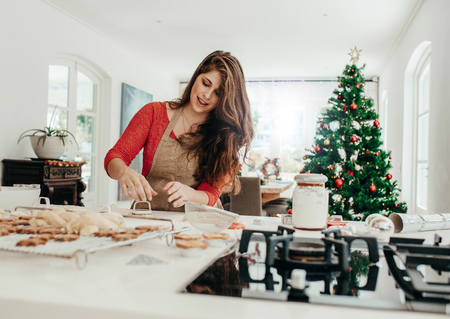 Photo for Young woman making shaped cookies with cutter for Christmas. Living room decorated with Christmas tree in the background. - Royalty Free Image
