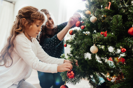 Foto de Mother and little daughter decorating Christmas tree at home. Little girl helping her mother in decorating Christmas tree. - Imagen libre de derechos
