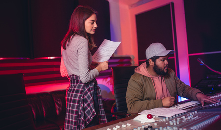 Photo for Female singer with man working on audio mixing console in recording studio. People working in professional music studio. - Royalty Free Image