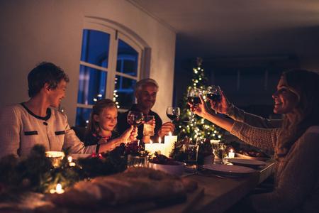 Foto de Three generation family enjoying christmas dinner together at home. Extended family toasting wine at christmas dinner. - Imagen libre de derechos