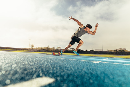 Foto de Runner using starting block to start his run on running track. Athlete starting his sprint on an all-weather running track with the help of starting block. - Imagen libre de derechos