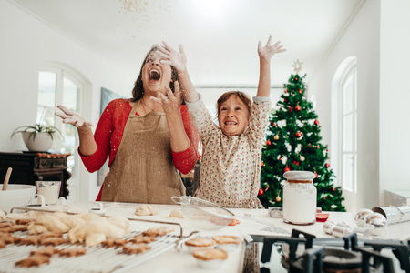 Foto de Happy mother and daughter in kitchen throwing flour in air while making cookies. Baked star cookies, muffins and gingerbread on kitchen table with decorated Christmas tree in the background. - Imagen libre de derechos