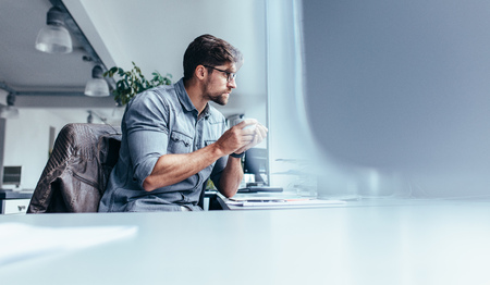 Foto de Businessman sitting in office with cup of coffee. Young man holding mug and looking away. - Imagen libre de derechos