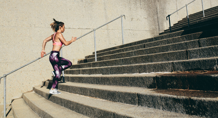 Photo pour Fitness woman running up on steps. Side view shot of female runner athlete going up stairs. - image libre de droit