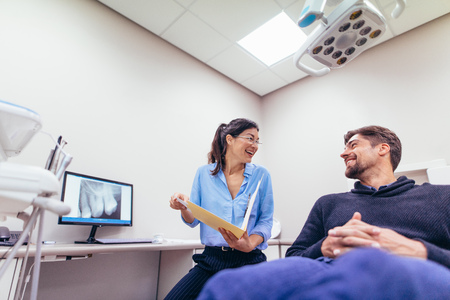Photo pour Happy dentist and patient at dental clinic. Smiling doctor and patient discussing report at dental clinic. - image libre de droit