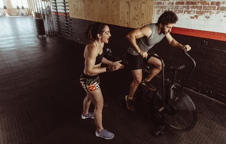 Foto de Personal trainer motivating man exercising on air bike in gym. Man doing intense workout on gym bike with female coach. - Imagen libre de derechos