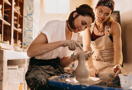 Photo pour Woman working on potters wheel making a clay pot. Woman potter making finishing touches to the clay pot on pottery wheel. - image libre de droit