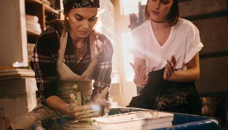Photo pour Woman potter teaching the art of pot making. Two women at a pottery workshop making clay pots. - image libre de droit