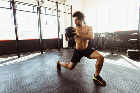 Foto de Core strength and stability workout. Fit and muscular man exercising with medicine ball at gym. - Imagen libre de derechos