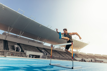 Foto de Runner jumping over an hurdle during track and field event. Athlete running a hurdle race in a stadium. - Imagen libre de derechos