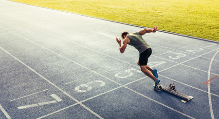 Photo pour Rear view of an athlete starting his sprint on an all-weather running track. Runner using starting block to start his run on race track. - image libre de droit