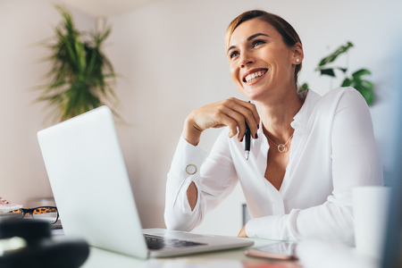 Foto de Smiling business woman sitting at her desk in office. Woman holding a pen with a laptop computer on her desk. - Imagen libre de derechos