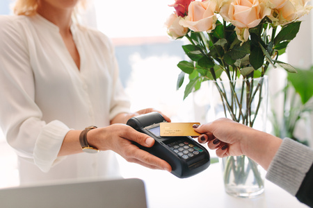 Foto de Hand of customer making payment through nfc technology credit card in the flower shop. Customer paying with contactless card at florist - Imagen libre de derechos