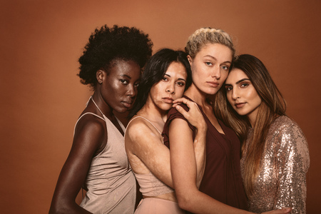 Photo for Group of diverse women standing together on brown background. Multi ethnic female friends looking at camera in studio. - Royalty Free Image