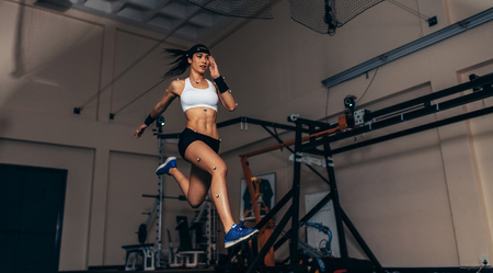 Photo pour Female athlete with motion capture sensors on her body running in biomechanical lab. Recording the movement and performance of sportswoman in sports science lab. - image libre de droit