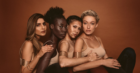 Photo for Portrait of female models with different skins. Group of young women sitting together and looking at camera on brown background. - Royalty Free Image