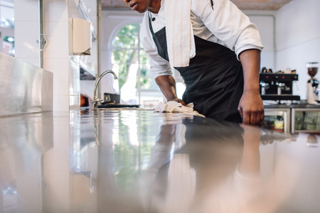 Foto de Cropped shot of waiter wiping the counter top in the kitchen with cloth. Man cleaning and maintaining commercial kitchen hygiene. - Imagen libre de derechos