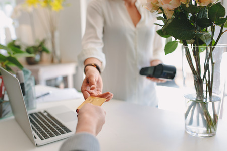 Photo for Young woman working at flower shop taking credit card from customer. Florist accepting debit card for payment from client. - Royalty Free Image