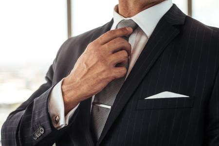 Foto de Cropped shot of businessman hand adjusting his necktie. Close up of man in business suit correcting tie. - Imagen libre de derechos