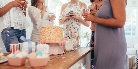 Photo pour Cropped shot of cake and sweet food on table with women standing around holding drinks at baby shower party. Female friends enjoying baby shower party. - image libre de droit
