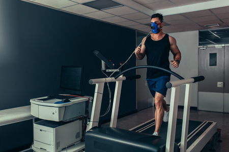Foto per Male runner with mask running on treadmill machine testing his performance. Athlete examining his fitness in biomechanics lab. - Immagine Royalty Free
