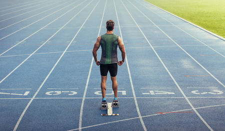 Foto de Rear view of an athlete ready to sprint on an all-weather running track. Runner using a starting block to start his run on race track. - Imagen libre de derechos