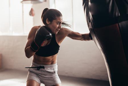 Photo pour Female boxer hitting a huge punching bag at a boxing studio. Woman boxer training hard. - image libre de droit