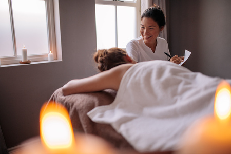Photo pour Beautician examining female client before spa treatment and making notes for the therapy. Female massage therapist talking to woman at wellness center and making notes. - image libre de droit