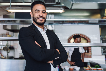 Photo for Portrait of young businessman standing in his restaurant with staff in kitchen. Proud restaurant owner standing with his arms crossed and looking at camera. - Royalty Free Image