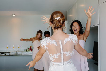 Photo for Bride and bridesmaids having fun in hotel room on wedding day. Bridesmaids hugging bride on wedding day. - Royalty Free Image