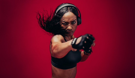 Photo for Boxer practicing her punches in a studio. African female boxer practicing boxing against red background. - Royalty Free Image