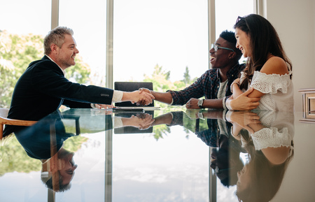 Photo for Male real estate broker shaking hands with new property owners while sitting across a table. Property seller congratulating couple on making deal on new house. - Royalty Free Image