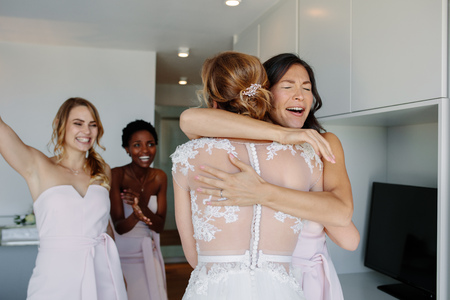 Photo for Happy bridesmaids congratulating bride in wedding gown in hotel room. Bridesmaids hugging the bride and smiling. - Royalty Free Image