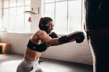 Photo for Female boxer hitting a huge punching bag at a boxing studio. Woman boxer training hard. - Royalty Free Image