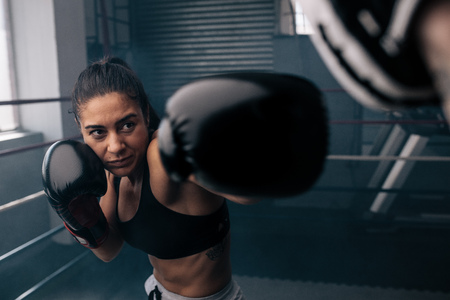 Photo pour Boxer practicing her punches at a boxing studio. Close up of a female boxer punching inside a boxing ring. - image libre de droit