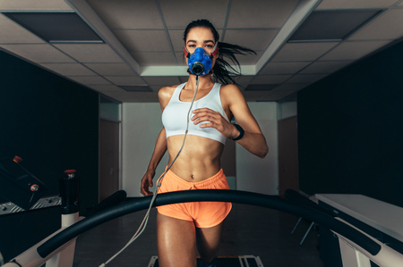 Photo pour VO2 max test. Sportswoman with mask running on treadmill. Female athlete in sports science lab measuring her VO2 max. - image libre de droit